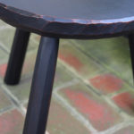 carved-edge milking stool, close-up